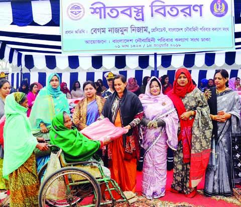 President of Bangladesh Noubahini Paribar Kalyan Sangha Begum Nazmun Nizam distributing winter clothes among the destitute at Nabik Colony ground in the city's Mirpur on Sunday.