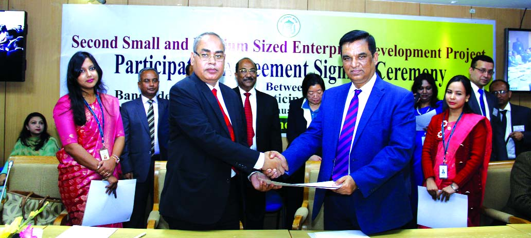 Md. Abdul Halim Chowdhury, Managing Director of Pubali Bank Limited and Md. Abul Bashar, General Manager of Financial Inclusion Department of Bangladesh Bank (BB), exchanging an agreement signing documents on