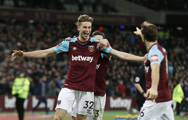 West Ham United's Reece Burke (left) celebrates after scoring the opening goal of the game in extra time during the English FA Cup third round replay between West Ham United and Shrewsbury Town at the London stadium in London on Tuesday.