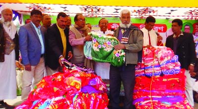 MODHUKHALI ( Faridpur): Former MP Alhaj Kazi Sirajul Islam distributing winter clothes among the distressed people at Modhukhali Central Eidgah ground on Thursday.