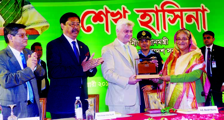 A crest being presented to Prime Minister Sheikh Hasina at the inaugural session of 4000th Parakendra at Mitingachhari in Kaptai Upazila through a video conferencing organised jointly by Parbatya Chattagram Development Board and UNICEF from a hotel in the city on Sunday.