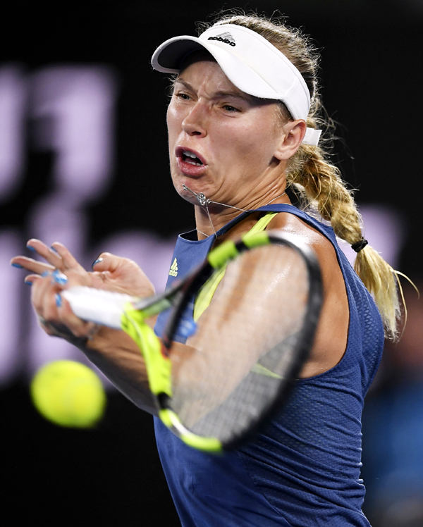 Denmark`s Caroline Wozniacki hits a forehand return to Spain`s Carla Suarez Navarro during their quarterfinal at the Australian Open tennis championships in Melbourne, Australia on Tuesday.