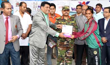 President of Bangladesh Amateur Boxing Federation Lieutenant General Aziz Ahmed handing over the Walton home appliance to a winner of Walton National Senior Boxing Competition at the Muhammad Ali Boxing Stadium on Saturday.
