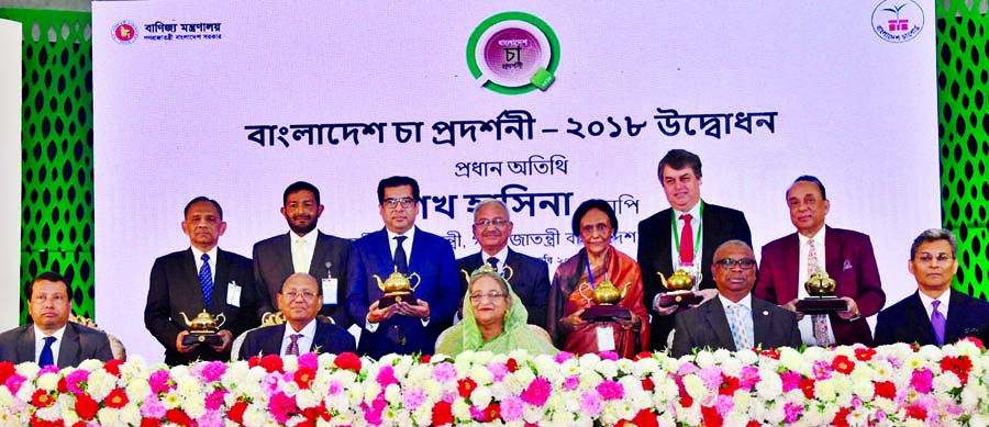 Prime Minister Sheikh Hasina at a photo session with the award recipients who played role in tea exporting and flourishing of tea industries at Bangabandhu International Conference Center in the city on Sunday.