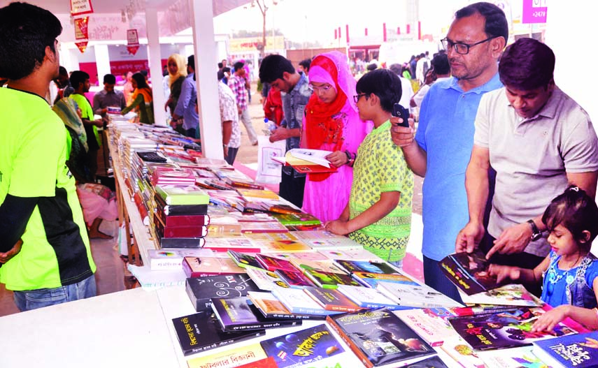 Buyers flip through the books at a stall of Amar Ekushey Book Fair on Bangla Academy premises in the city on Monday.