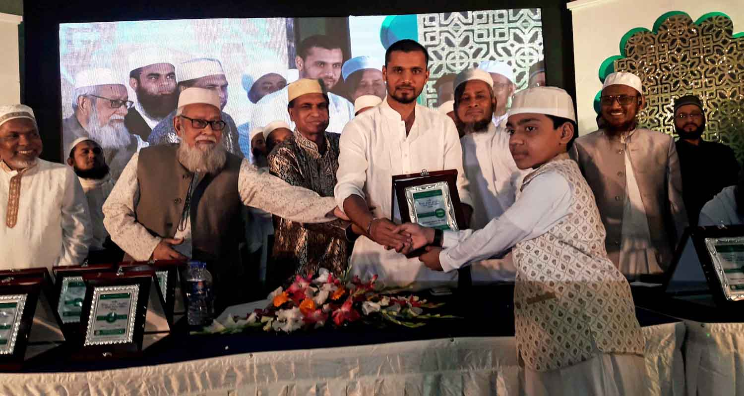 Captain of Bangladesh National Cricket (ODI) team Mashrafe Bin Mortaza handing over a crest of honour to Hafiz Yasin Arafat at the Bashundhara International Convention Centre in the city recently. Yasin Arafat became Hafiz-e-Quran in 86 days. He was a student of Tanjimul Ummah Hifz Madrasah of Cox's Bazar. Ahlul Huffaz Foundation Bangladesh arranged the reception programme.