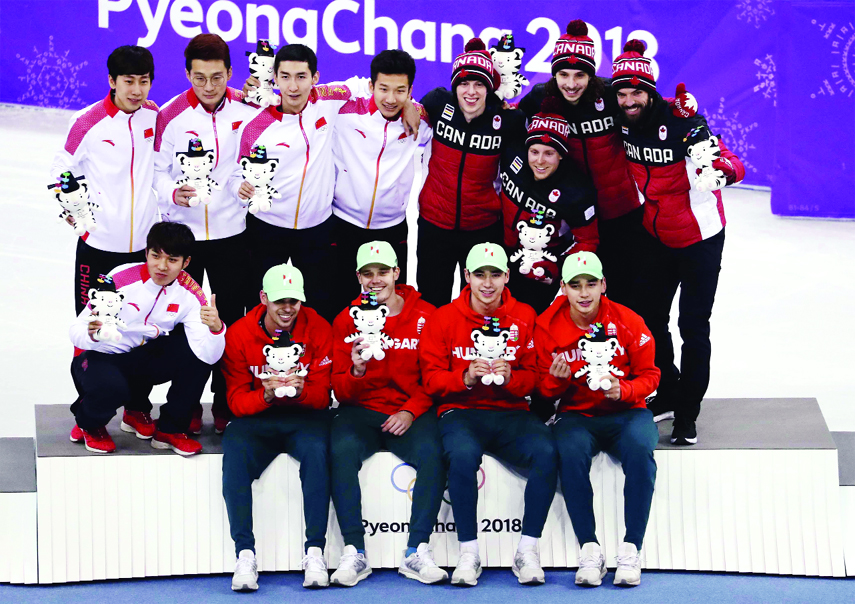 Gold medalists, Hungary men's 5000 meters short track speedskating relay team (foreground) pose for a photo with silver medalists China (back left) and bronze medalists Canada (background right) on the podium in the Gangneung Ice Arena at the 2018 Winter Olympics in Gangneung, South Korea on Thursday.