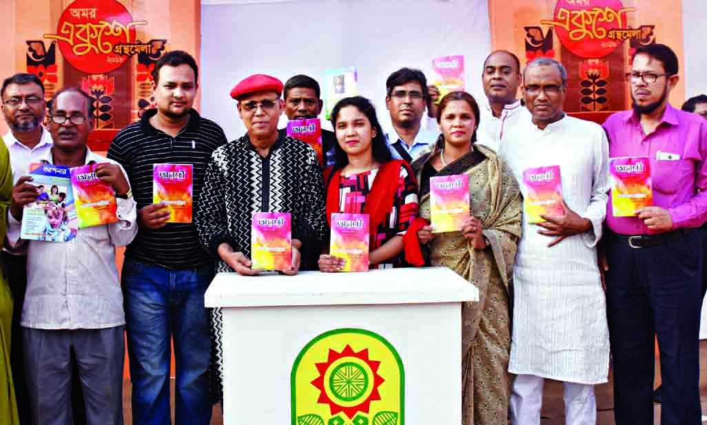 Poet Abdul Hai Shikder along with others holds the copies of a book titled 'Aroni' written by Latiful Khabira at its cover unwrapping ceremony in the city's Suhrawardy Udyan on Saturday.