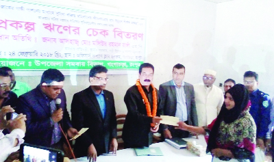 GANGACHHARA (Rangpur) : State Minister for LGRD and Cooperatives Mashiur Rahman Ranga distributing cheque for loan among the members of cooperative society yesterday.