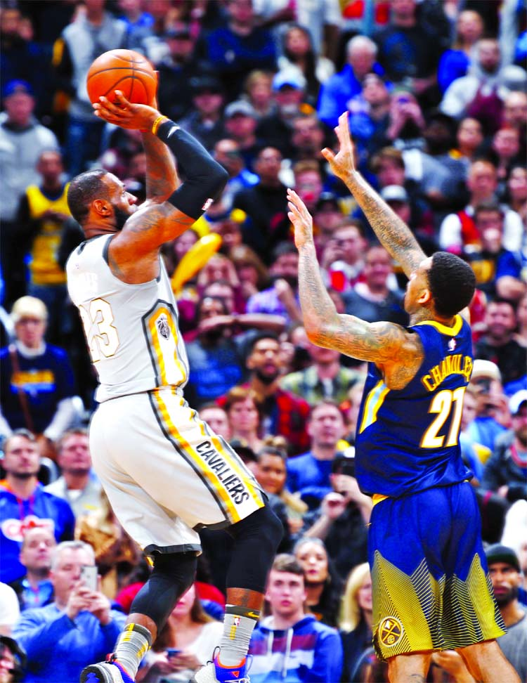 99ee940c4ba2 Cleveland Cavaliers forward LeBron James (left) shoots and scores over  Denver Nuggets forward Wilson Chandler late in the second half of an NBA  basketball ...