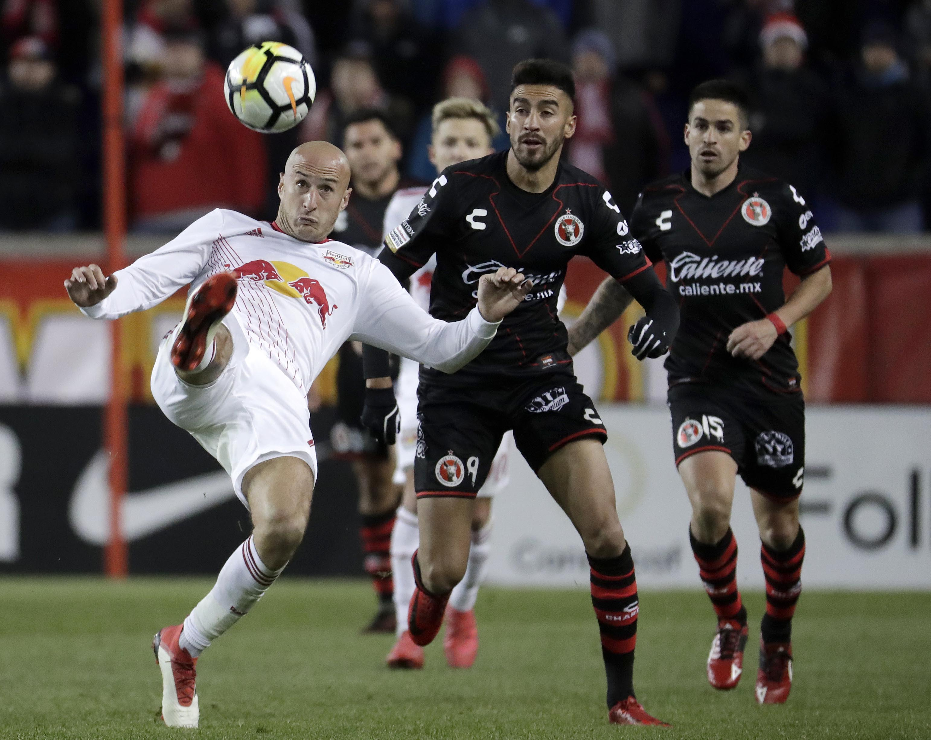New York Red Bulls defender Aurelien Collin (front) tries to clear the ball away as Tijuana forward Juan Martin Lucero (center) and defender Damian Perez look on during the second half of a CONCACAF Champions League quarterfinal soccer match on Tuesday in Harrison, N.J. The Red Bulls won 3-1.