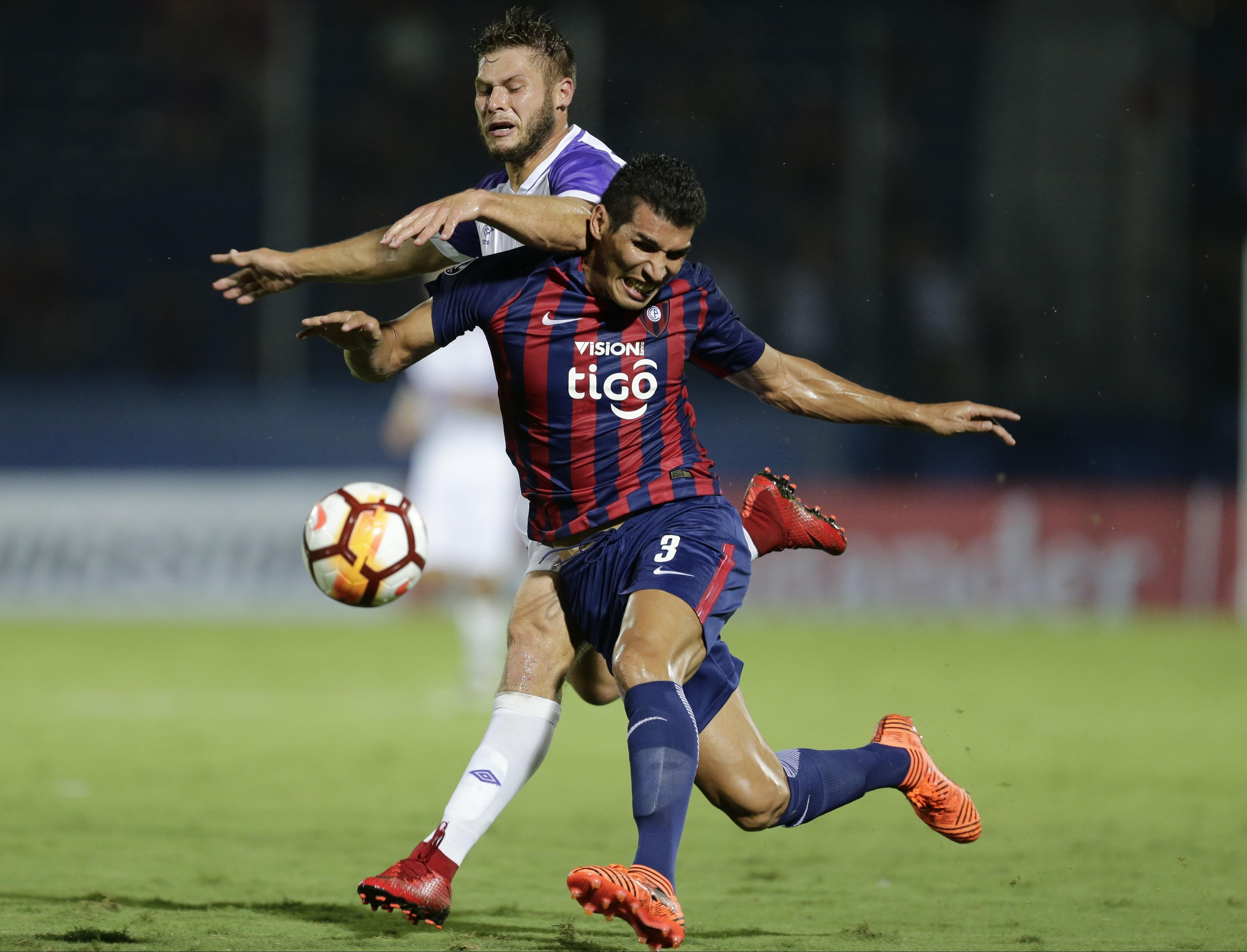 German Rivero (back) of Uruguay's Defensor Sporting fights for the ball with Cristian Insaurralde of Paraguay's Cerro Porteno during a Copa Libertadores Soccer game in Asuncion, Paraguay on Tuesday.