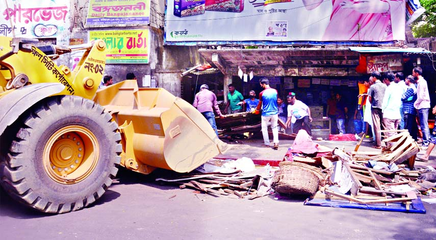 DSCC dismantling illegal structures set up at roadside on city's Topkhana Road on Saturday.