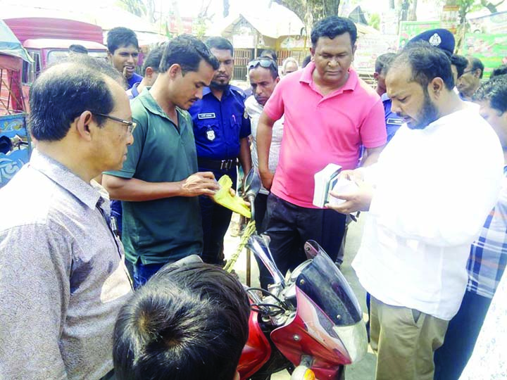 BETAGI  (Barguna):  Members of mobile court  checking  a motor cycle at Betagi  Poura Town on the occasion of the World Consumers'  Day recently .