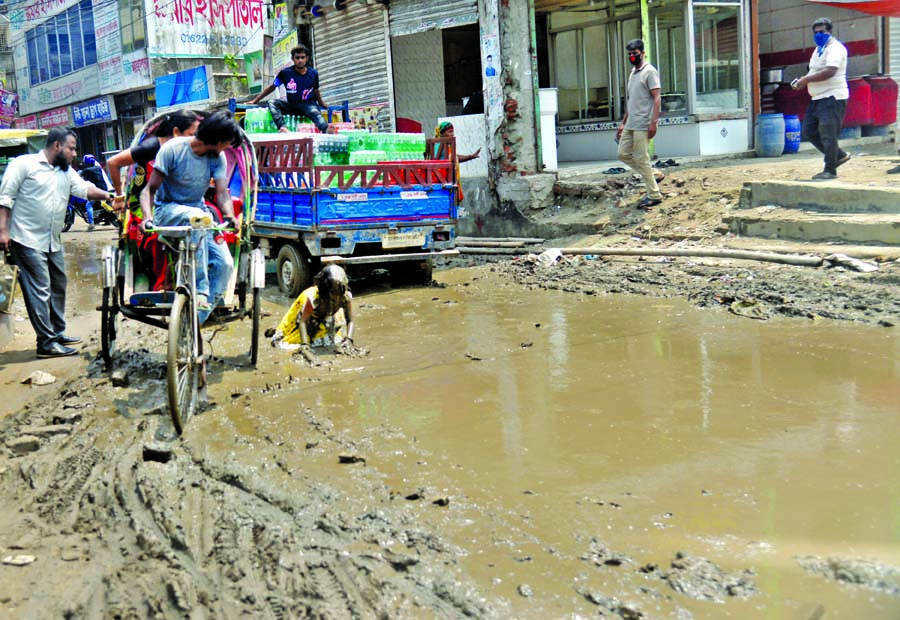 A teenage girl is struggling to recover from a knee deep muddy water on a road at Chunkutia in Keraniganj on the outskirts of the city. Such accidents often take place in the busy road but there is none to take care.
