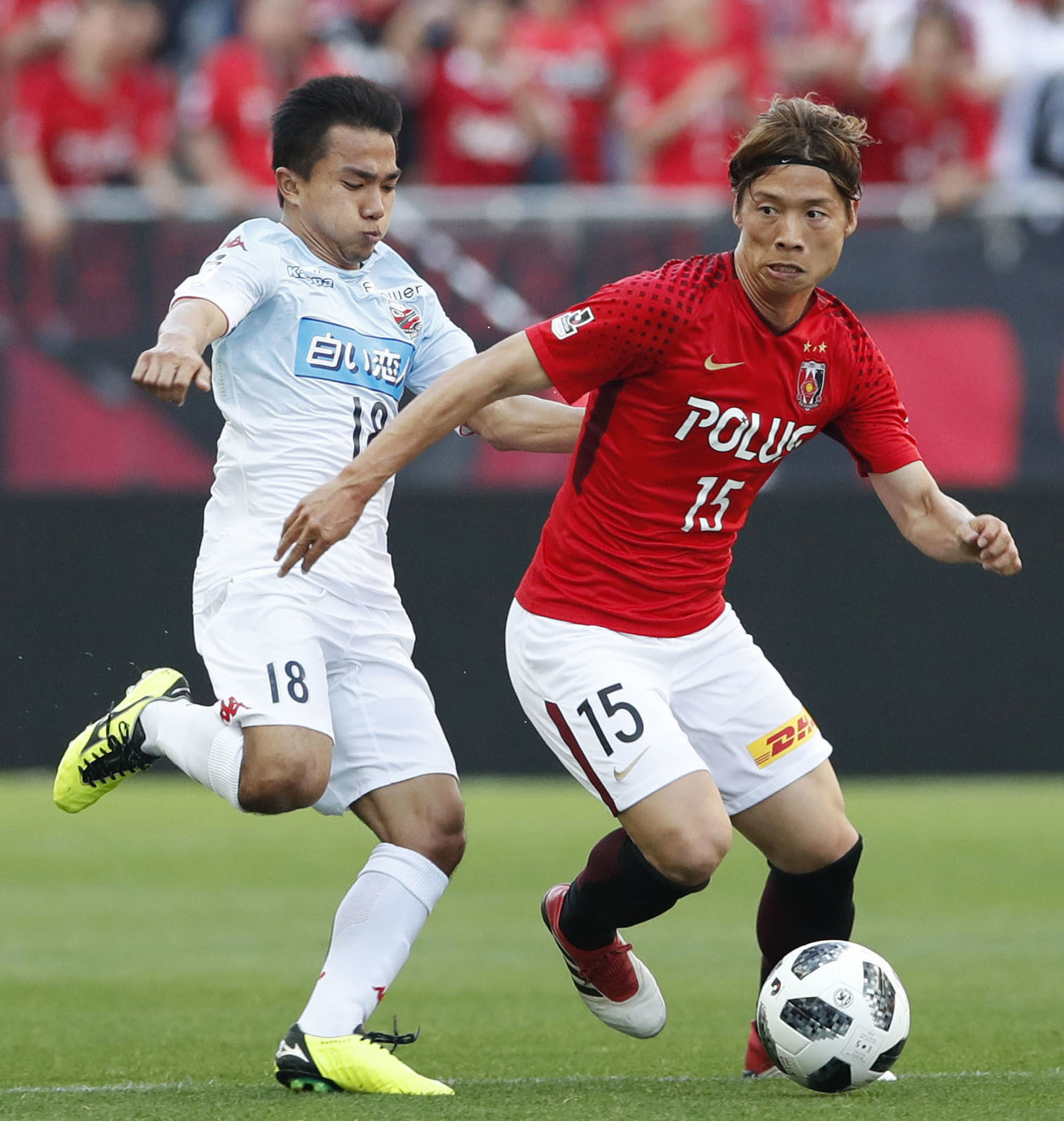 Chanathip Songkrasin (left) of Consadole Sapporo and Kazuki Nagasawa (right) of Urawa Reds fight for the ball during their J1 League match at Saitama Stadium in Saitama, north of Tokyo on Saturday.