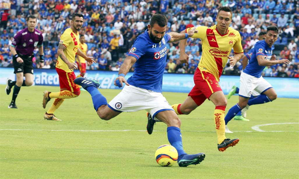 Cruz Azul's Martin Cauteruccio (center) ready to strike the ball as Morelia's Carlos Rodriguez attempts to stop him during a Mexico League soccer match between Cruz Azul and Morelia at Azul Stadium in Mexico City on Saturday. This is the last match the Cruz Azul will ever play at Azul Stadium.