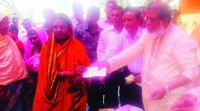 SAGHATA(Gaibandha): Deputy Speaker of Jatiya Sangsad  Adv Md Fazle Rabbi Miah MP distributing loan among the poor women  of Kukhatair Nari Unnoyan Samabay Samity Ltd  at Saghata Upazila on Sunday.