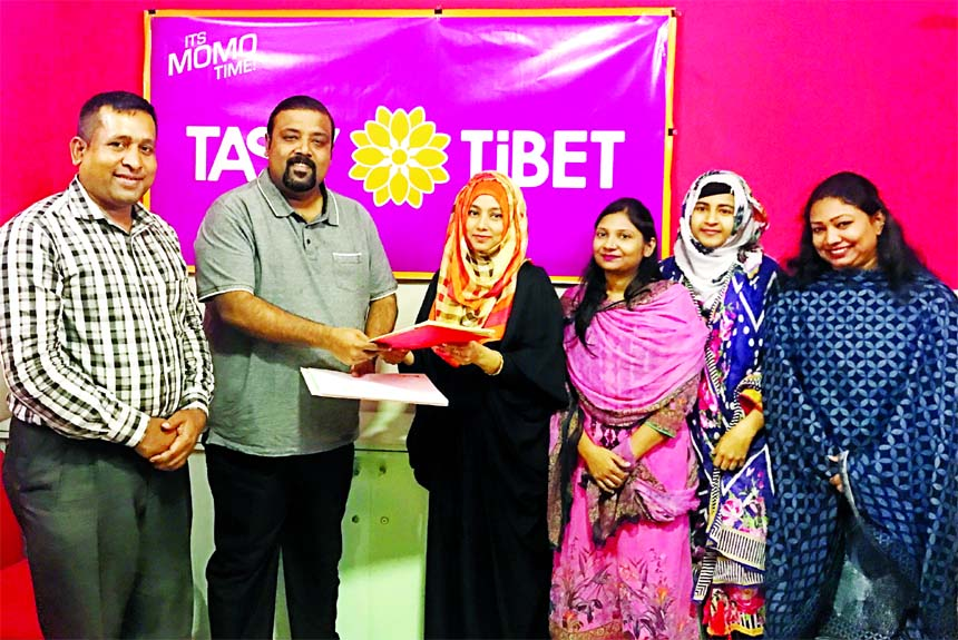 Sabbir Rahman Tanim, Managing Director of Tasty Tibet Limited and Hafyzun Nessa, Managing Partner of Taeam (a readymade food supplier company), exchanging an agreement signing documents at its office in the city on Tuesday. High officials from both the organizations were also present.