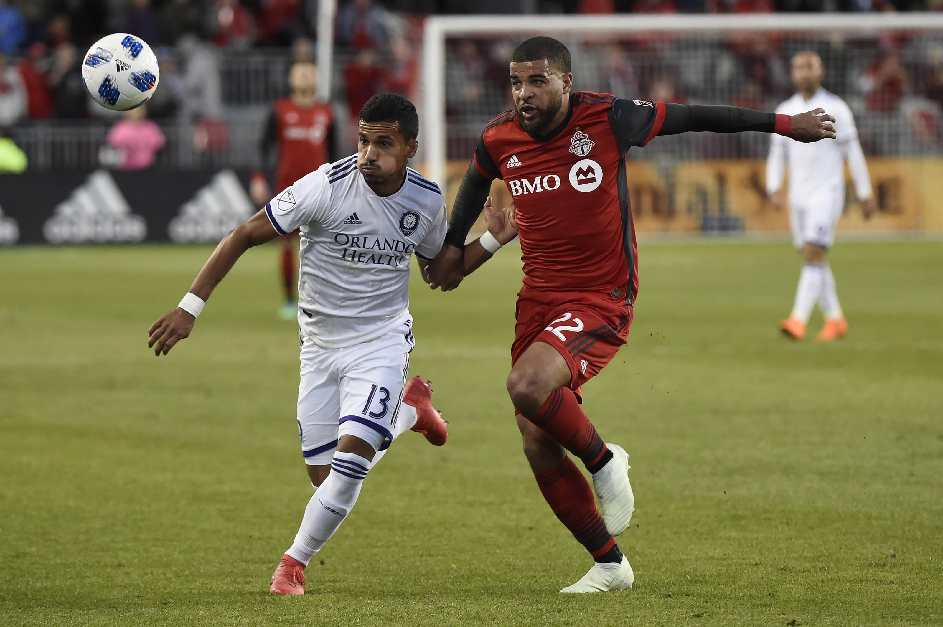 Toronto FC forward Jordan Hamilton (22) and Orlando City defender Mohamed El-Munir (13) chase the bouncing ball during the first half of an MLS soccer match in Toronto on Friday.