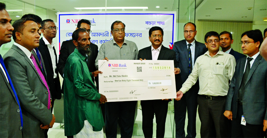 Md. Mehmood Husain, Managing Director of NRB Bank Limited, handing over a cheque to Tuku Sheikh, a farmer as Agri Loan at Bogra Branch recently as a part of Argi-Loan Disbursement Project. Imran Ahmed FCA and Chief Operating Officer, Rahat Shams, Head of Retail Banking, Mohammed Abu Shayem, Head of SME of the bank and Abedur Rahman, DGM of Bangladesh Bank were present.