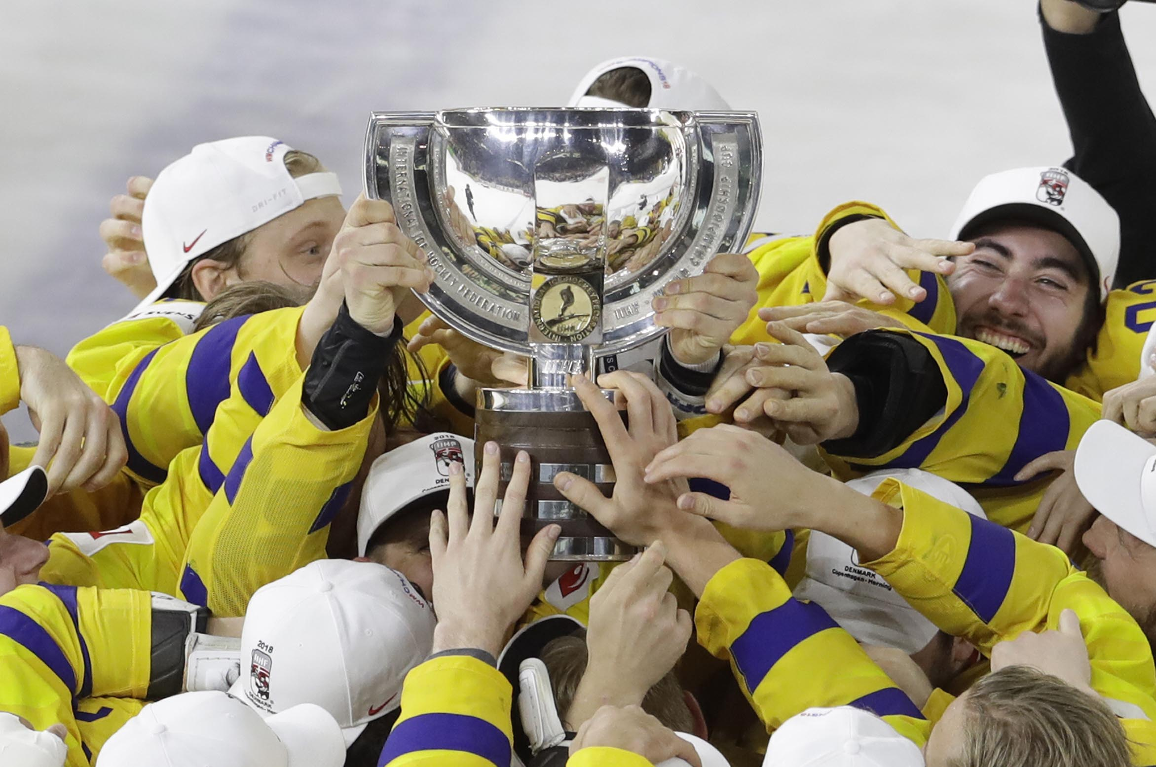 Sweden's players celebrate with the trophy their victory over Switzerland in the Ice Hockey World Championships final match between Sweden and Switzerland at the Royal arena in Copenhagen, Denmark on Sunday.
