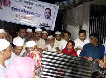MA Latif MP distributing relief goods among the fire-affected people in Chattogram city yesterday.