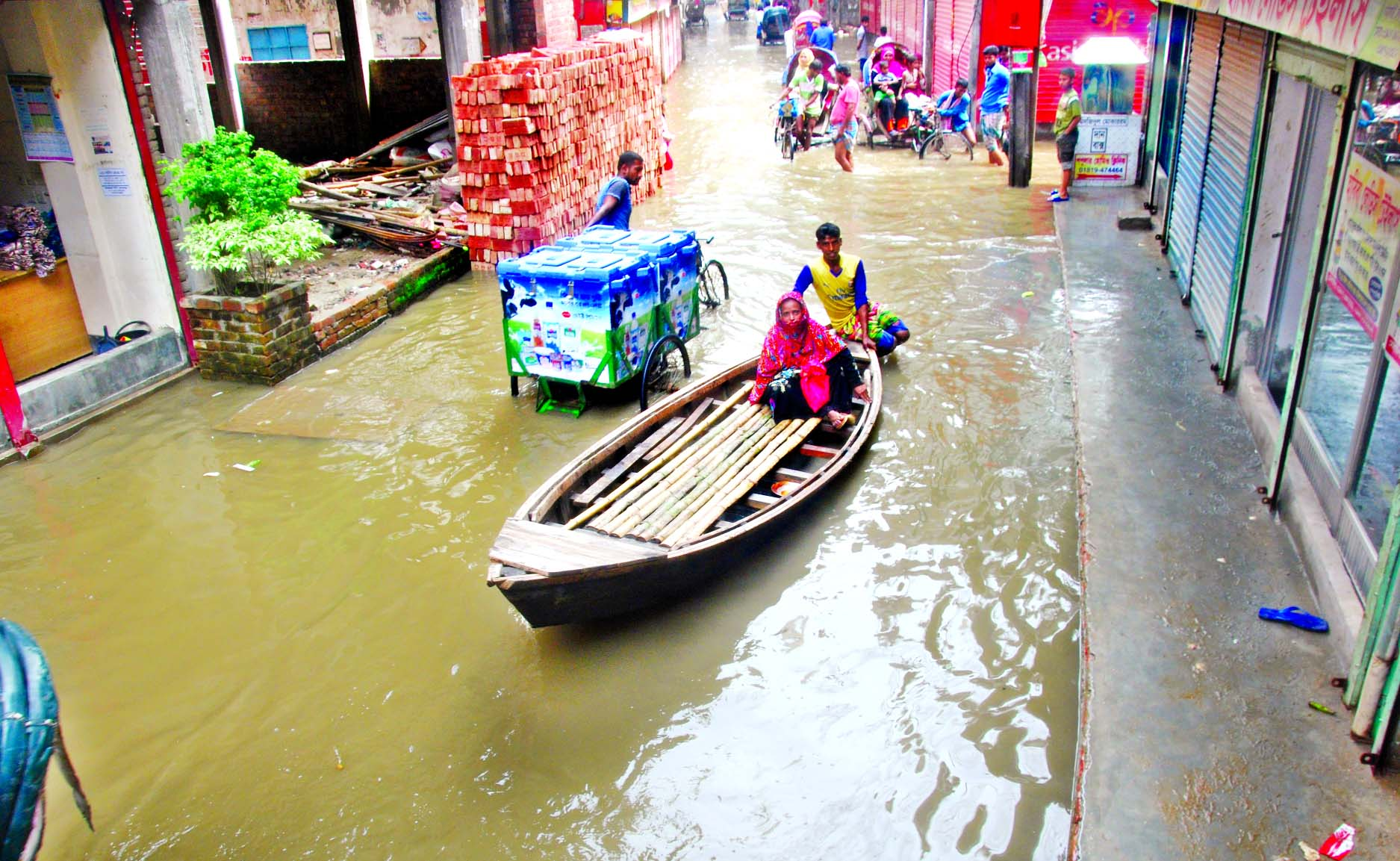 The main thoroughfare at Ragerbagh area went under knee deep water as rain waters are stagnant for a few days. Locals using boat side by side with-rickshaw, van to help pass the pedestrians as transport during this monsoon.