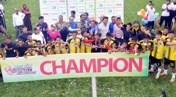 Members of Saif Sporting Youth team, the champions of the Saif Power Battery 5th BKSP Cup Under-18 Football Tournament with the guests and officials of BKSP pose for a photo session at the BKSP Ground in Savar on Tuesday.