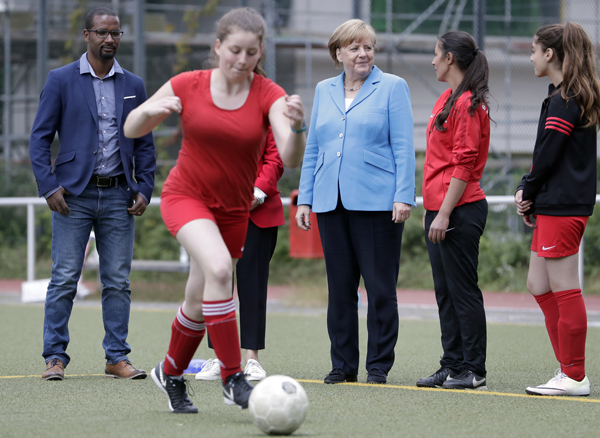 German Chancellor Angela Merkel (center) and the former German national soccer team player and integration commissioner of the German soccer association, Cacau (right) attend a women soccer training session at a soccer club in Berlin, Germany on Wednesday.