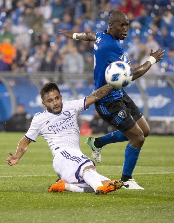 Orlando City midfielder Josue Colman kicks the ball away from Montreal Impact defender Rod Fanni during the second half of an MLS soccer match on Wednesday in Montreal.