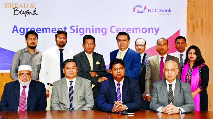 Muhammad H Kafi, Head of Cards of NCC Bank Ltd and Noor A Alam Chowdhury, Chairman of Bread & Beyond, exchanging the agreement documents at the bank head office recently. Mosleh Uddin Ahmed, Managing Director, Khondoker Nayeemul Kabir, Md. Habibur Rahman, Deputy Managing Directors of NCC Bank and Md. Asifuzzaman, Managing Director of the food company were also present.