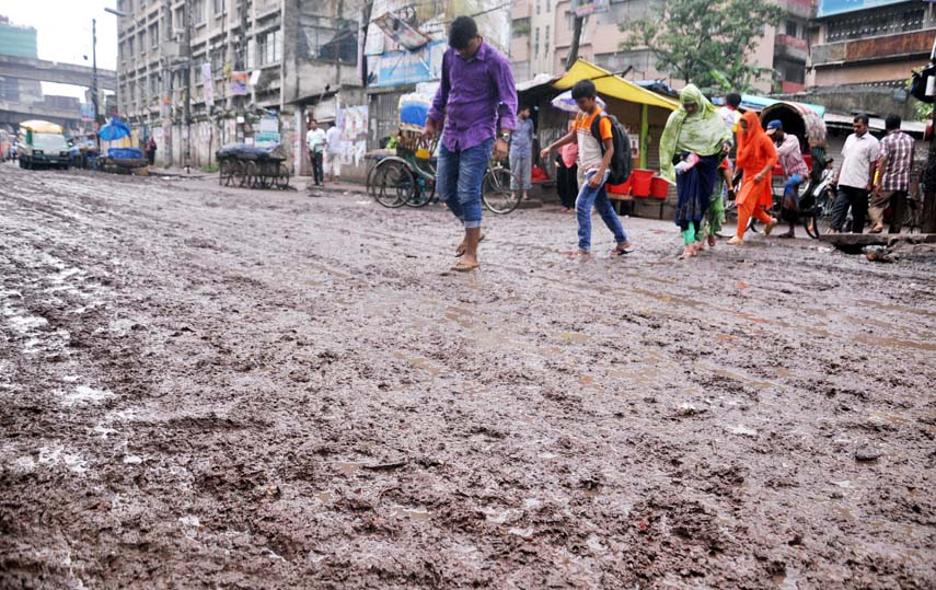 Pedestrians passing through a muddy road as the authority concerned does not repair the road for long time. The snap was taken from Bibir Bagicha area in the city's Jatrabari on Tuesday.