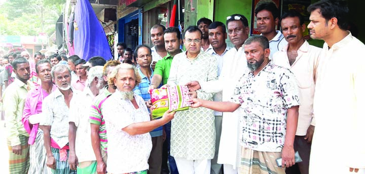 BANARIPARA(Barishal): Golum Faruk, Chairman, Banaripara Upazila distributing Eid clothes among the  rickshaw, van and construction labourers recently.