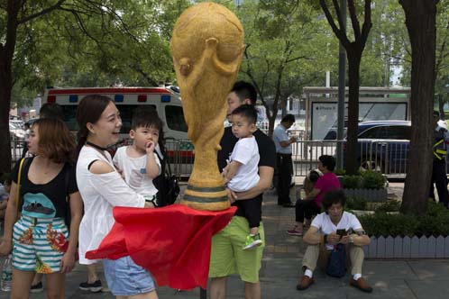 Huang Xin (seated bottom right) waits near the replica trophy he made from human hair in the likeness of the FIFA World Cup to coincide with the 2018 soccer World Cup held in Russia on the streets of Beijing, China on Monday. According to the artist Huang Xin, 2.18 kg. (4.8 lb.) of human hair from as many as 56 ethnicities in China collected over the past four years were used in the creation of the trophy.