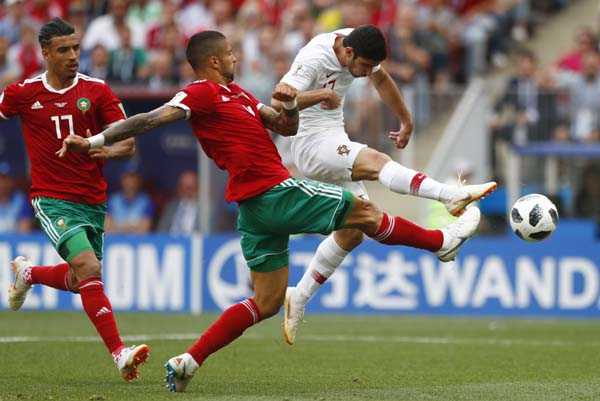 Portugal's Goncalo Guedes (right) shots on target as Morocco's Manuel Da Costa (center) challenges for the ball during the group B match between Portugal and Morocco at the 2018 soccer World Cup at the Luzhniki Stadium in Moscow, Russia, Wednesday. Portugal won the match 1-0.