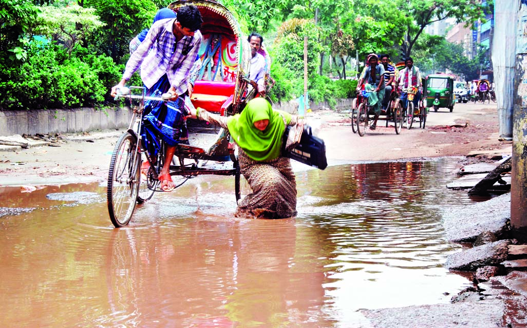 A woman fell into a ditch on a water logged road in the city as her rickshaw hit the pothole endangering her life. This photo has been taken on Wednesday from Rajarbagh area.