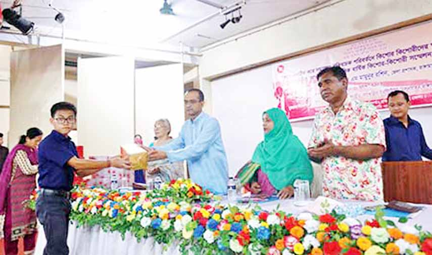 A teenagers' conference was held at the Small Ethnic Group Cultural Institute Auditorium in Rangamati town on Friday. The photo shows a teenage boy receiving a gift from DC AKM Mamunur Rashid.