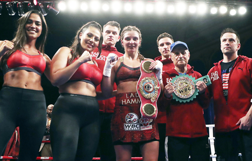 Christina Hammer, of Germany, holds her championship belts after defeating Tori Nelson during their WBC and WBO women's middleweight championship boxing bout on Friday.