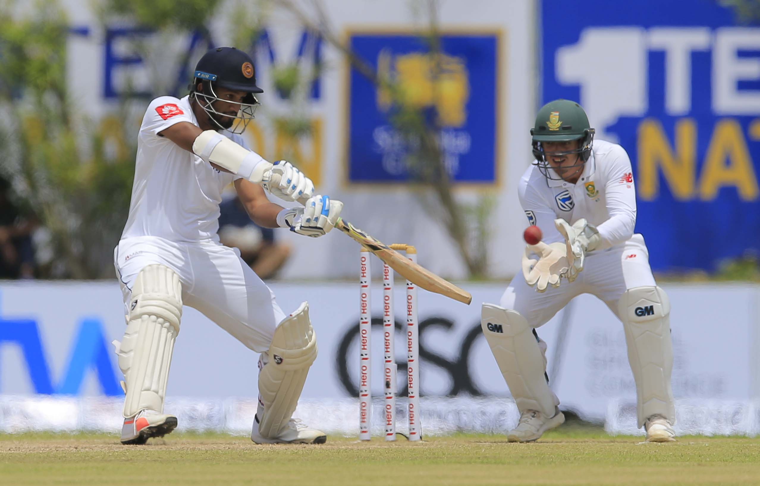 Sri Lanka's Dimuth Karunaratne plays shot as South Africa's Quinton de Kock watches during the first day's play of their first Test cricket match in Galle, Sri Lanka on Thursday.