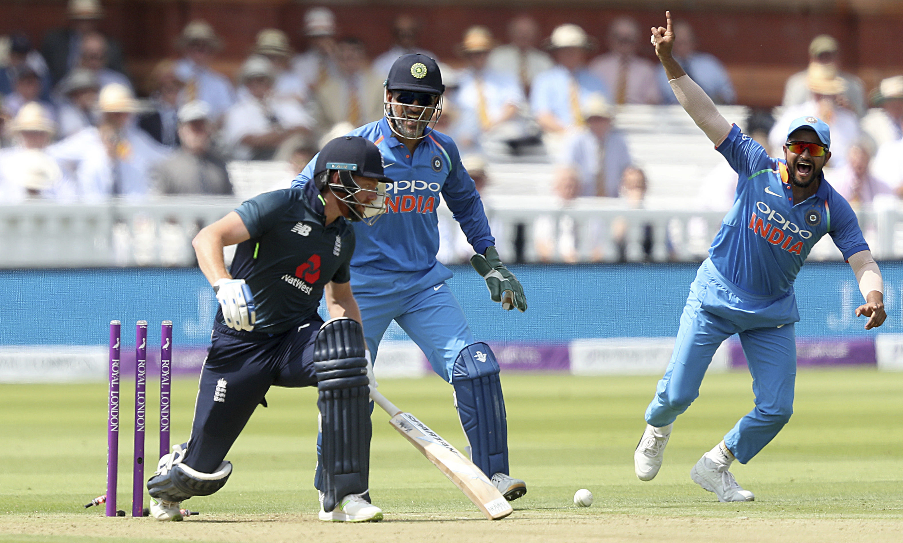 India's MS Dhoni (centre) celebrates as England's Jonny Bairstow is bowled out by India's Kuldeep Yadav (not pictured) during the second one day international cricket match between England and India at Lord's, London on Saturday.