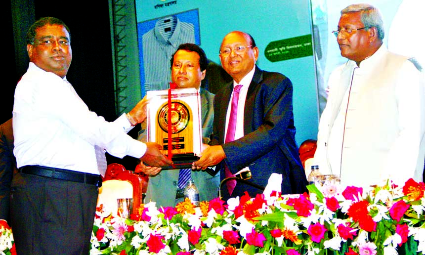 Sk. Momin Uddin, Managing Director of S.A.F Industries Limited, a sister concern of Akiz Group, is seen receiving the award (Gold) for outstanding contributions in export of leather sector for the year 2014-2015 from Commerce Minister Tofail Ahmed at Omani Memorial Auditorium  in the city on Sunday.