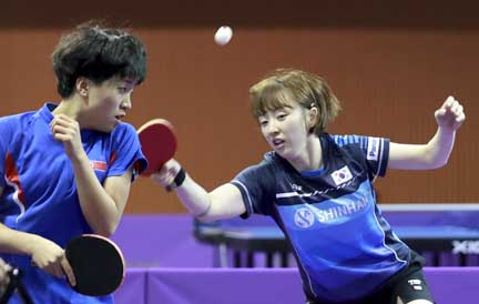 Combined team's South Korean Suh Hyo-won (right) returns a shot with teammate North Korean Kim Song I (left) during their women doubles preliminary round match against Uzbekistan's Olga Kim and Regina Kim at the ITTF World Tour Korea Open table tennis in Daejeon, South Korea on Wednesday.
