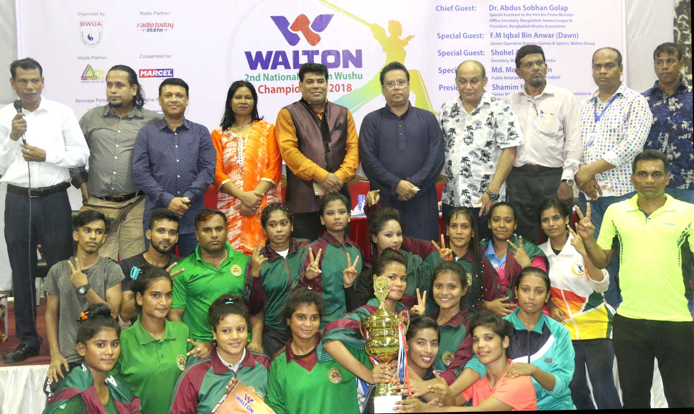 Bangladesh Ansar, the champions of the Walton 2nd National Women's Wushu Championship with the guests and officials of Bangladesh Wushu Association pose for a photo session at the Gymnasium of National Sports Council on Thursday.