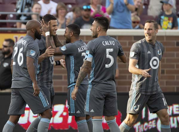 Minnesota United forward Christian Ramirez (21) is congratulated by teammate Alexi Gomez (32) after his goal during the first half of an MLS soccer match against the New England Revolution in Minneapolis on Wednesday.