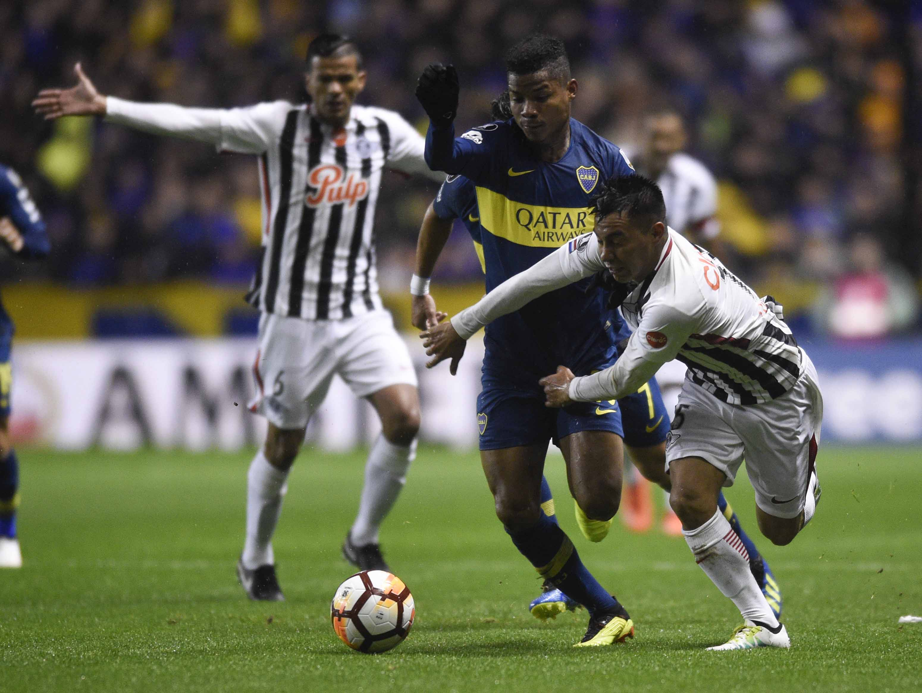 Angel Lucena (right) of Paraguay's Libertad, fights for the ball with Wilmar Barrios (center) of Argentina's Boca Juniors, during a Copa Libertadores soccer match in Buenos Aires, Argentina on Wednesday.