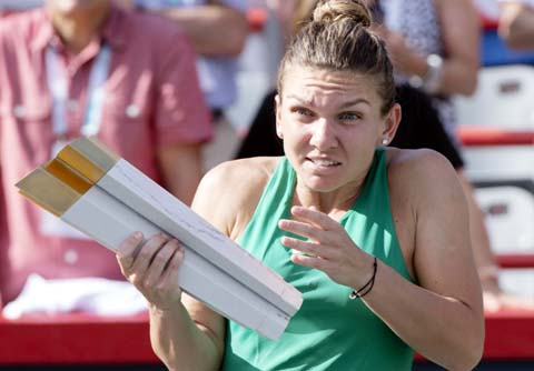 Simona Halep of Romania, reacts as the streamer cannon is fired during the victory ceremony after defeating Sloane Stephens of the United States in the final at the Rogers Cup women's tennis tournament in Montreal on Sunday.