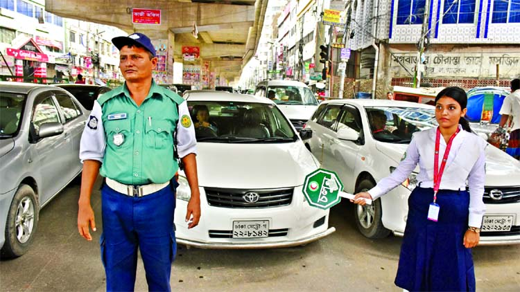 A girl scout in cooperation with traffic police trying to create awareness among the people about traffic discipline on roads. This photo was taken from Moghbazar area on Monday.