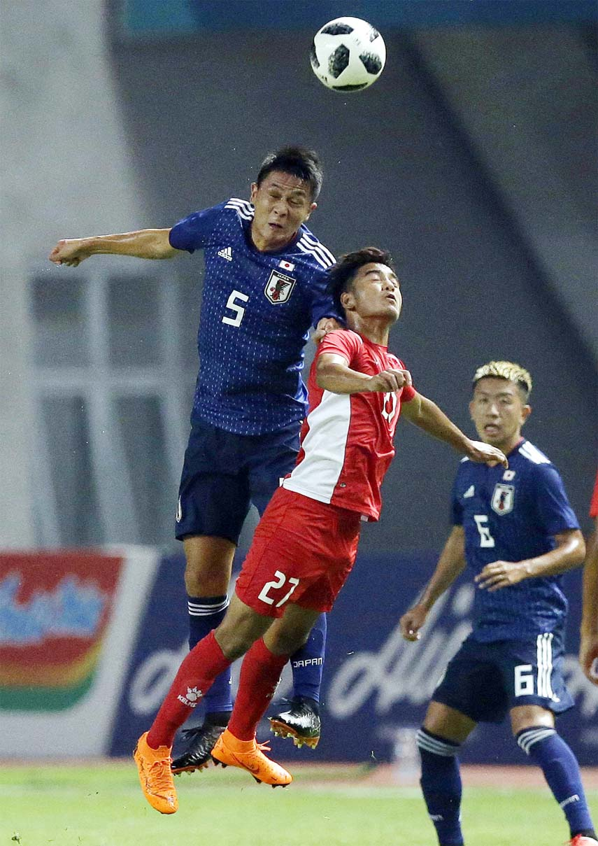 Japan's Daiki Sugioka (left) battles for the ball with Nepal's Abishek Rijal during their men's soccer match at the 18th Asian Games at Wibawa Mukti Stadium in Cikarang, Indonesia on Tuesday.