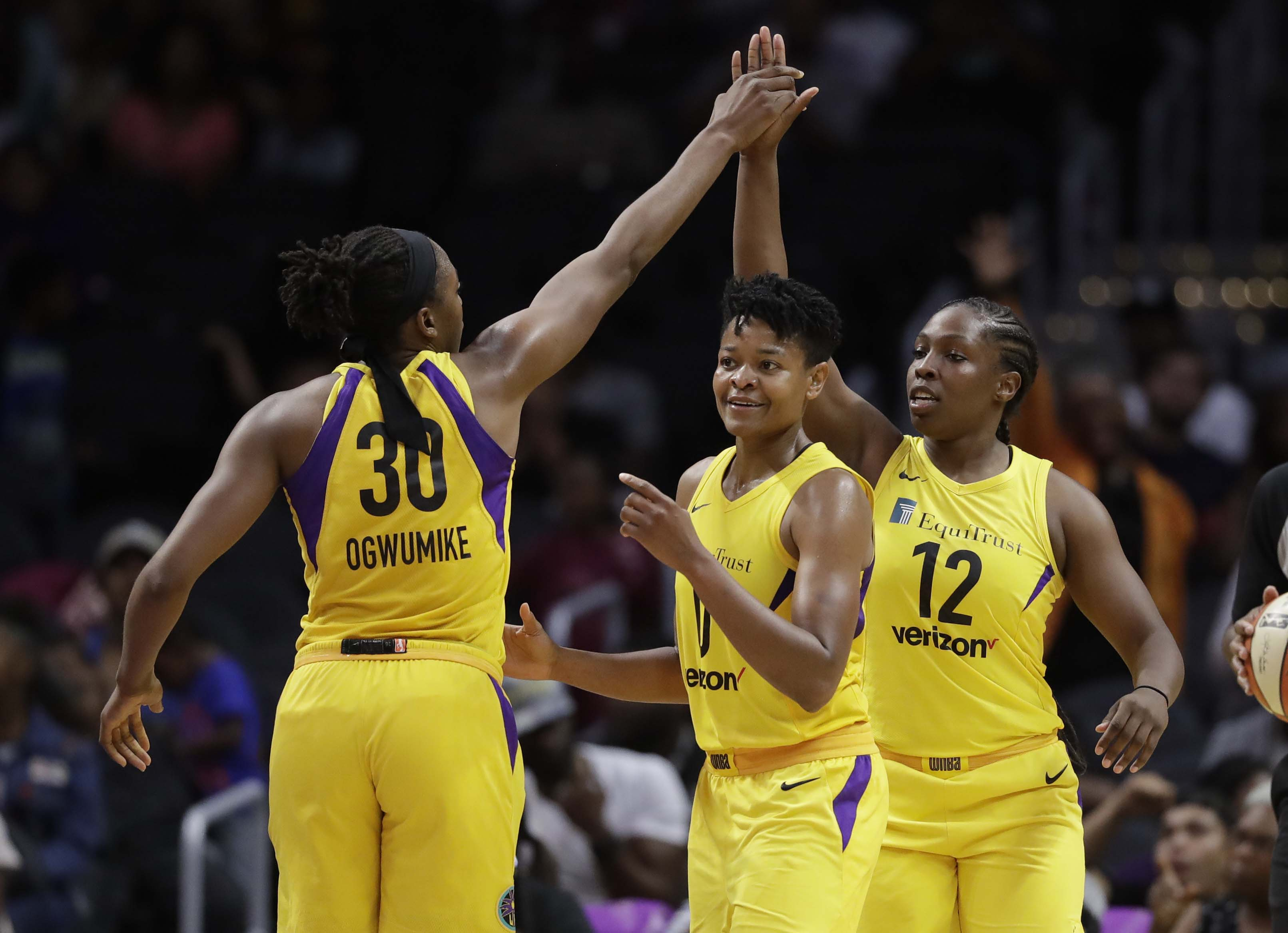 Los Angeles Sparks' Chelsea Gray (12) celebrates her basket with teammates Nneka Ogwumike (30) and Alana Beard during the second half of a WNBA basketball game against the New York Liberty in Los Angeles on Tuesday.